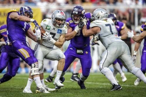 Ballträger der Vikings wird von zwei Defensiv-Spielern der Raiders geblockt. Am Bild Leon Balogh (Vikgins), Sandro Platzgummer (Raiders), Christoph Gombkötö (Vikings) und Dominik Bauer (Raiders)