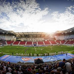 Stadionpanorama Austrian Bowl 2017 Fans im Vordergrund und die untergehende Sonne über dem Stadiondach im Westen